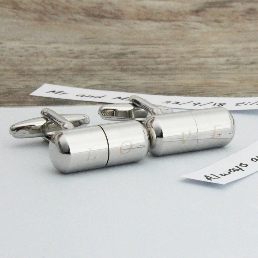 Metal capsule cuff links engraved with the letters L, O, V, and E