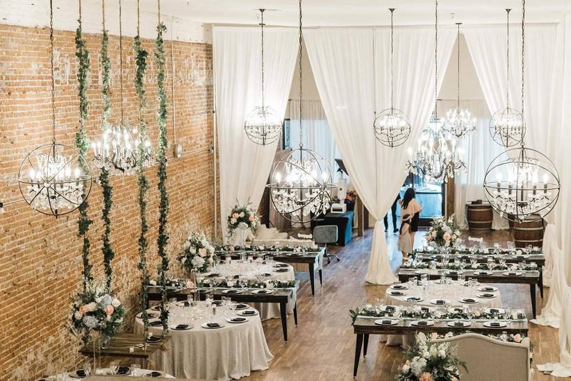 indoor wedding reception in industrial space with brick walls and spherical hanging light fixtures
