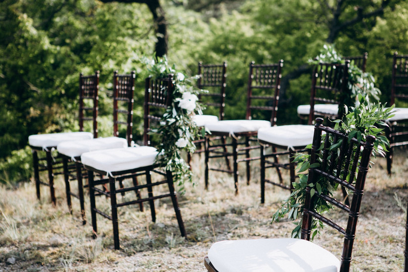 empty wedding chairs with greenery