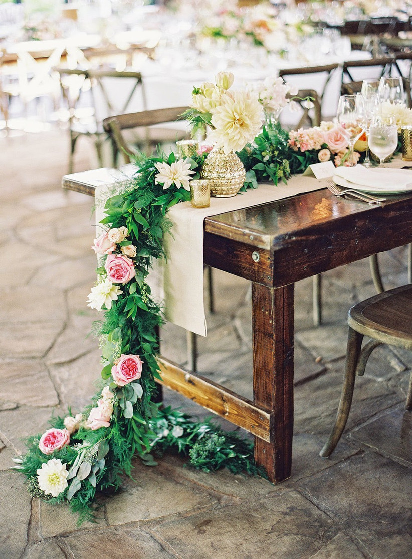 greenery and rose flower garland hanging off the end of a dark wooden table