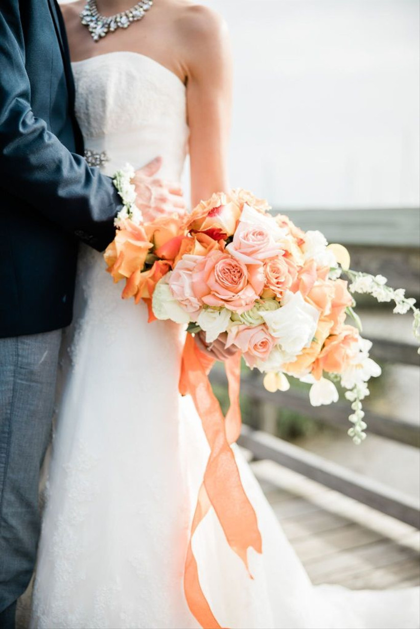 bride holds pale orange blush and white beach wedding bouquet with roses and tulips