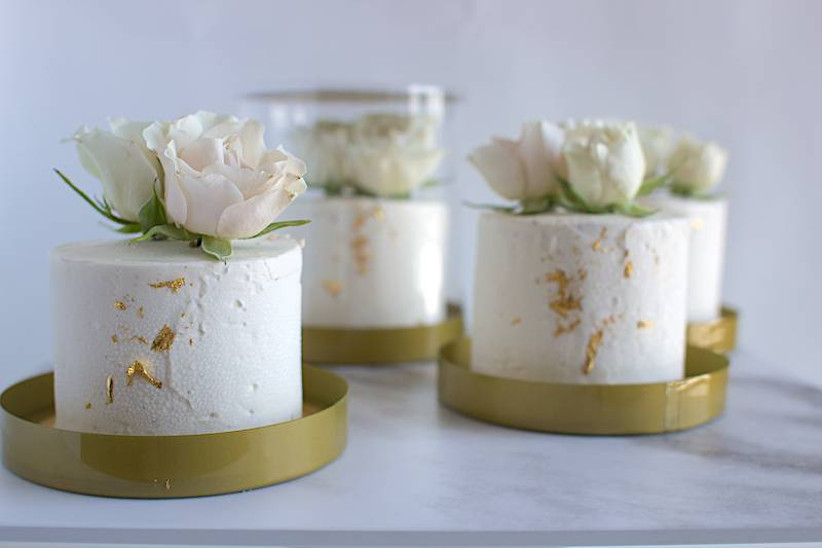 close-up of miniature wedding cakes decorated with white buttercream frosting and pink roses
