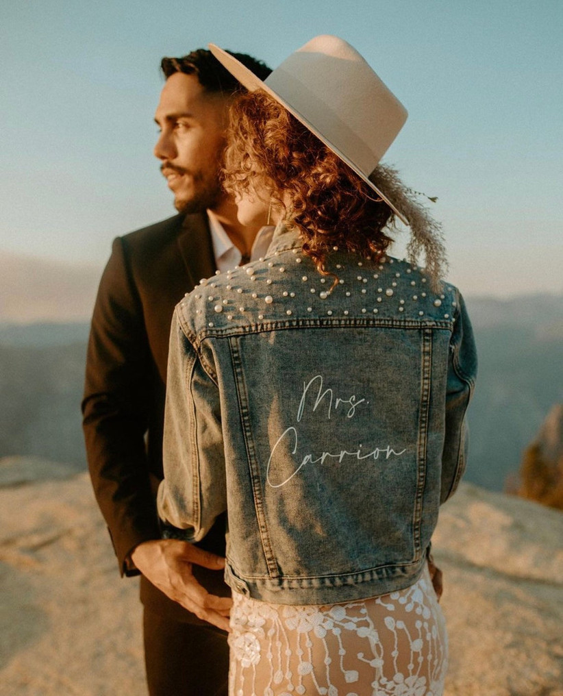 denim bridal jacket with pearls sewn across the back of shoulders and bride's last name written in white calligraphy on the back
