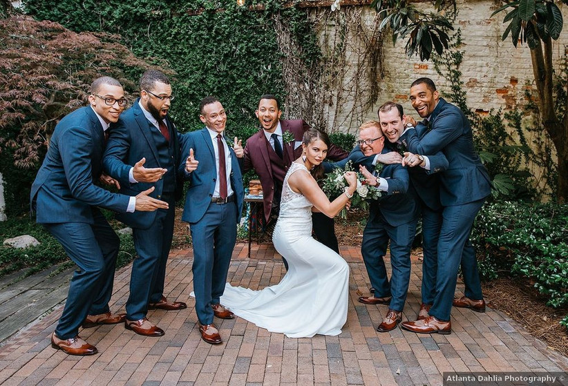 groom and groomsmen pose with the bride