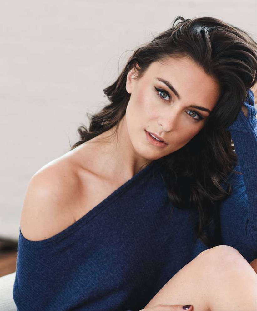 boudoir session with clothes on - bride wears blue off-the-shoulder sweater and looks into camera