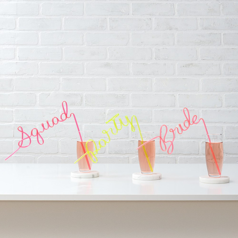 Three cocktail glasses with pink and yellow silly straws spelling Squad, Party, and Bride