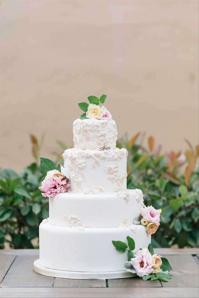 white fondant wedding cake decorated with pale pink and yellow flowers