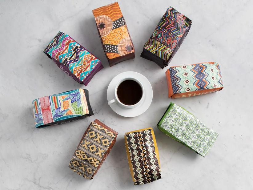 Colorful bags of gourmet coffee placed around a cup of coffee