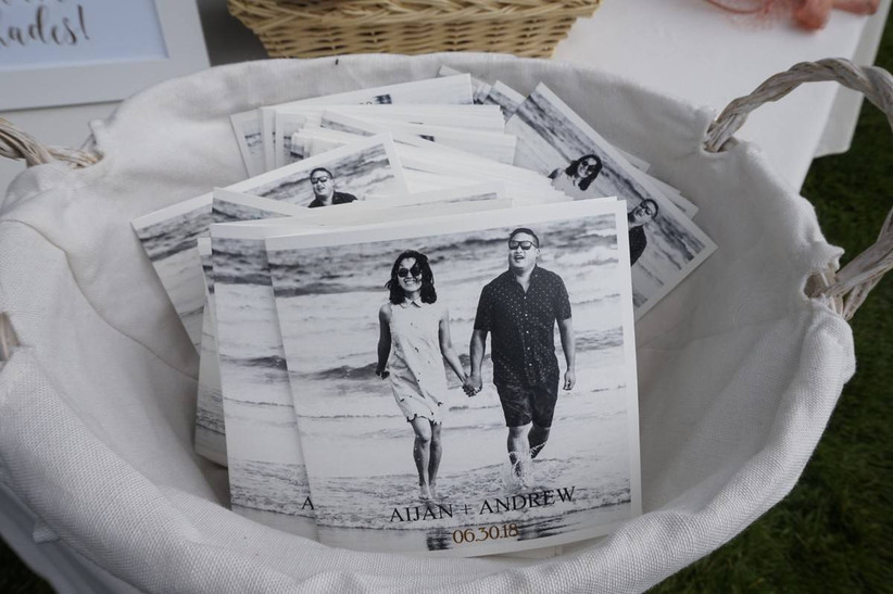 basket of wedding ceremony program booklets with black and white engagement photos on the cover