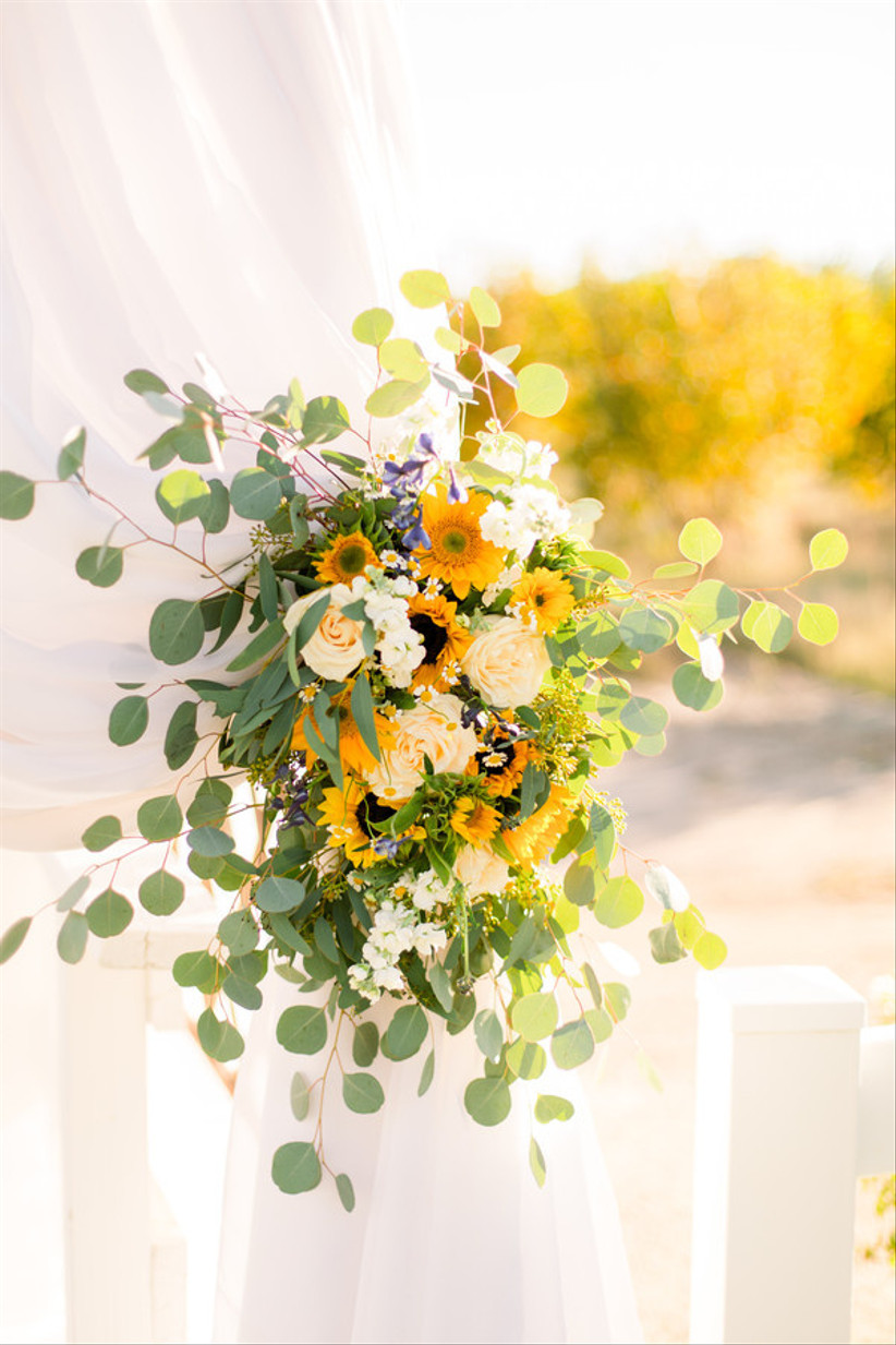 white sheer curtain tied back with sunflower arrangement of eucalyptus and white flowers