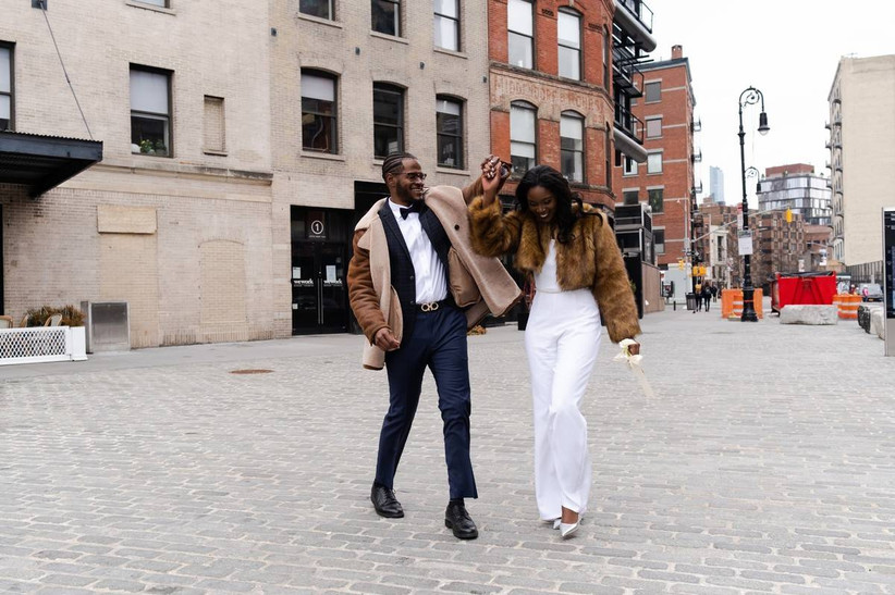 Black couple walking through New York City smiling laughing holding hands groom is twirling bride