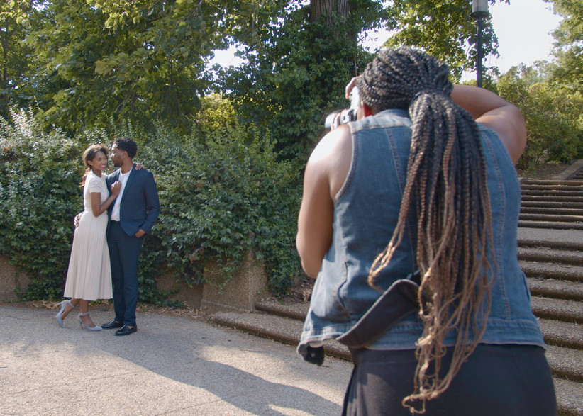 Action shot of Black photographer capturing engagement photos of young Black couple
