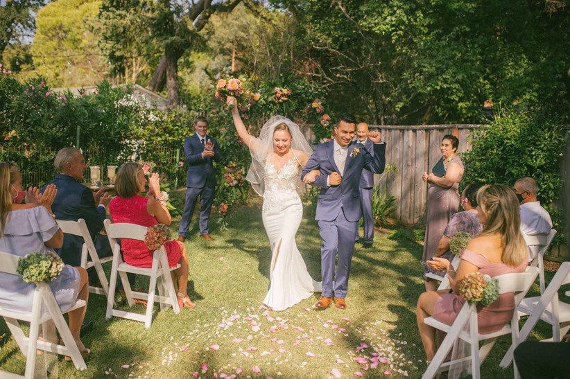 bride and groom celebrate walking down the aisle after backyard wedding ceremony