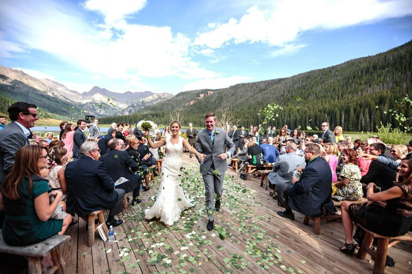 couple exiting wedding ceremony with mountain backdrop