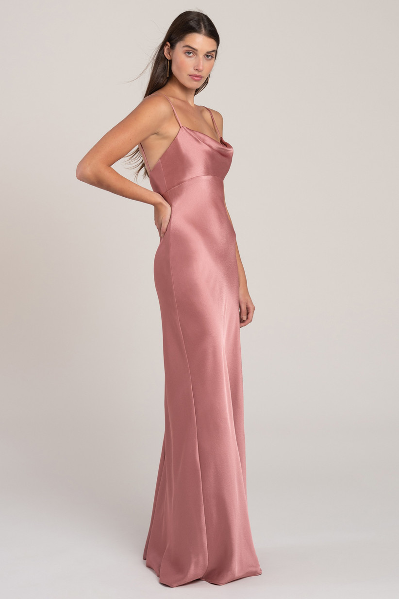 model poses from the side while wearing a floor-length mauve satin bridesmaid dress trend