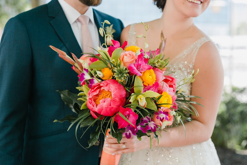 colorful beach wedding bouquet with bright pink peonies and green cymbidium orchids and yellow ranunculus