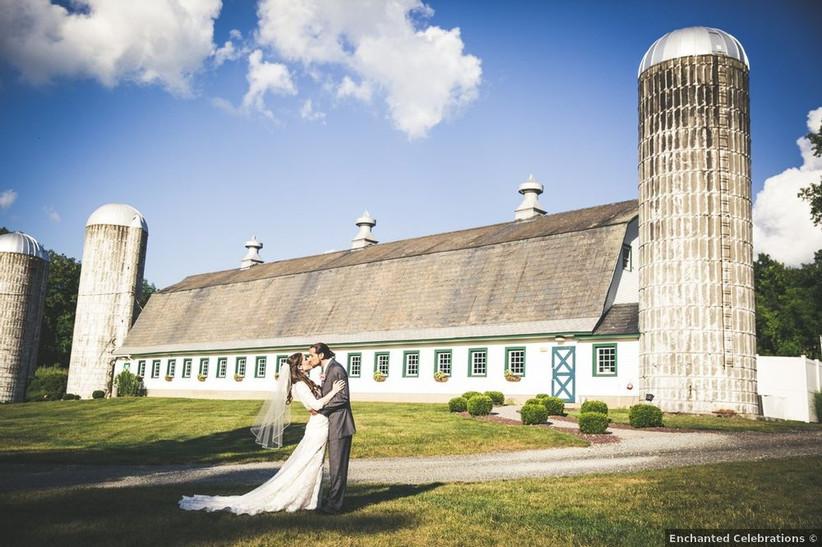 bride and groom kissing outside barn