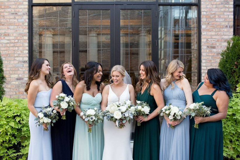 bride and her bridesmaids laugh while standout outside of the venue they are wearing mis-matched dresses in green and blue colors