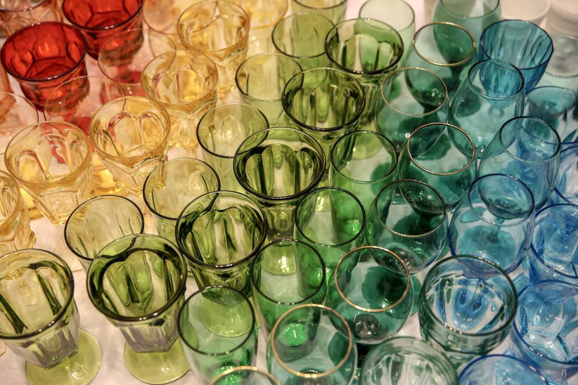 rainbow wedding theme idea rows of colorful vintage glassware in blue, yellow, red, and green arranged by color