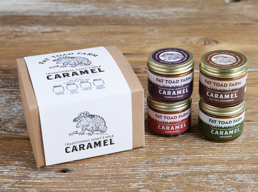 Box of Fat Toad Farm traditional goat's milk caramel with four jars stacked next to it in different flavors