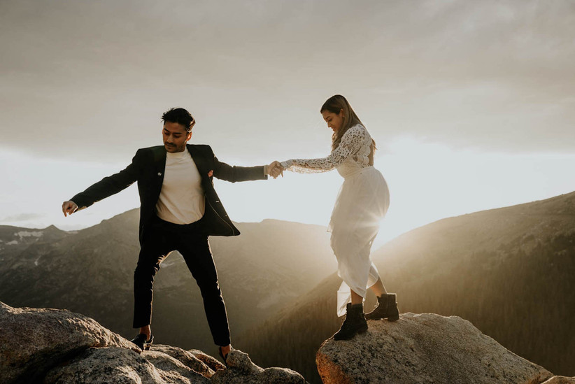 bride and groom holding hands as they walk across rocks on top of a mountain at sunset