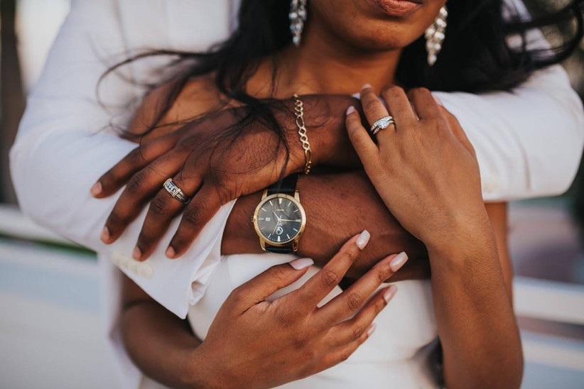 close up of Black couple's hands and arms as groom hugs bride from behind