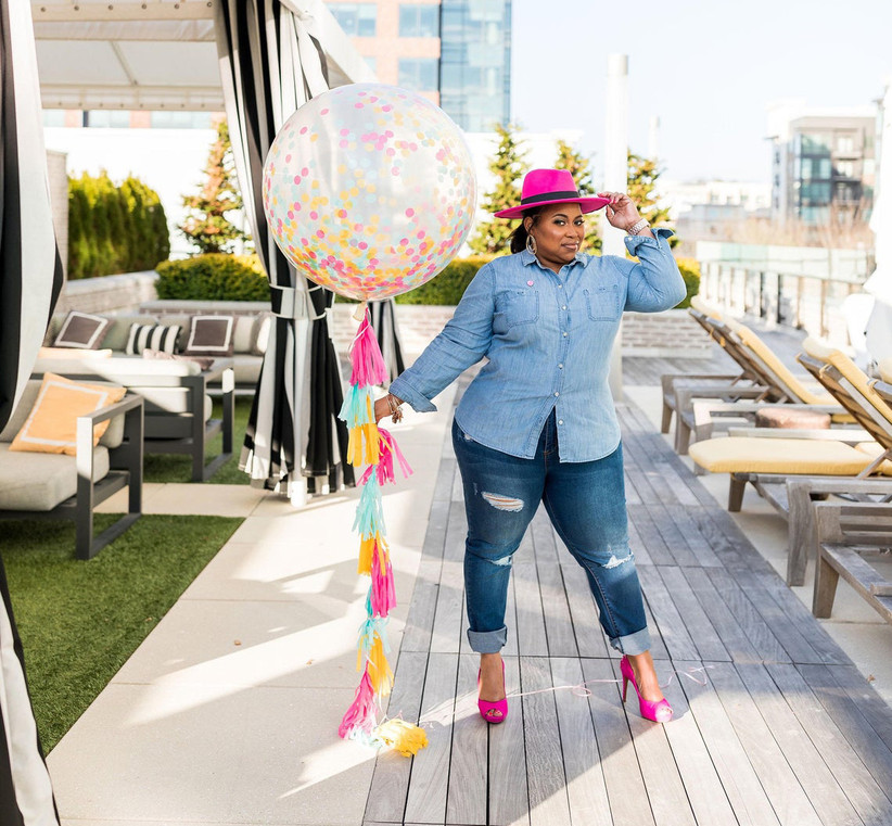 Woman posing in pink heels and a pink hat holding giant confetti balloon with colorful tassels