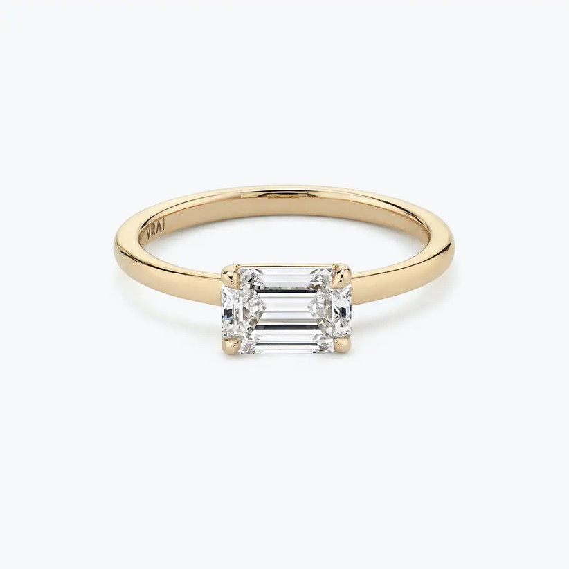 Sideways emerald-cut solitaire diamond engagement ring with plain gold band