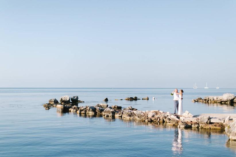 bride and groom standing on rocky coastline over ocean