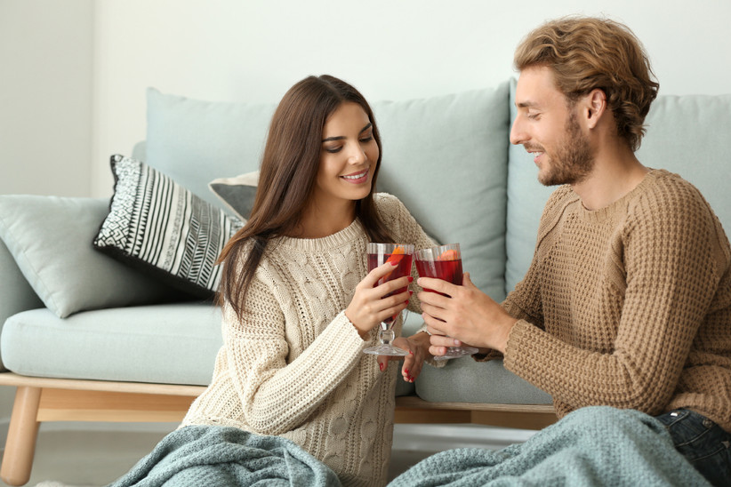 Cozy couple toasting cocktail glasses at home