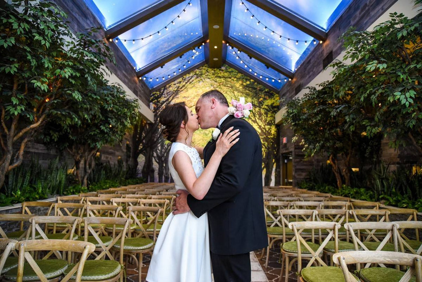bride and groom kiss at las vegas wedding chapel with skylights and faux trees along the walls