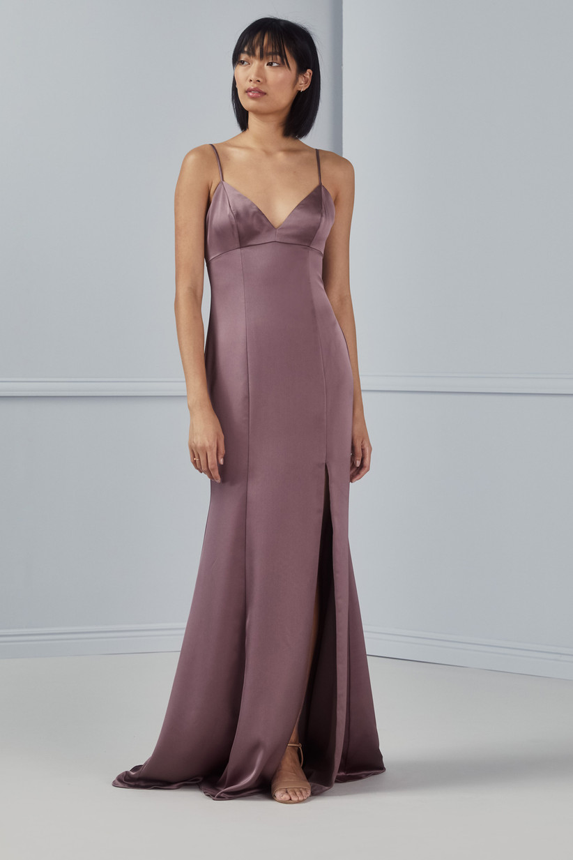Model looks off to the side while wearing formal floor-length mauve bridesmaid dress with side slit and empire waist
