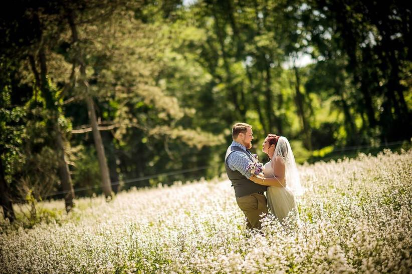 bride and groom hugging in meadow