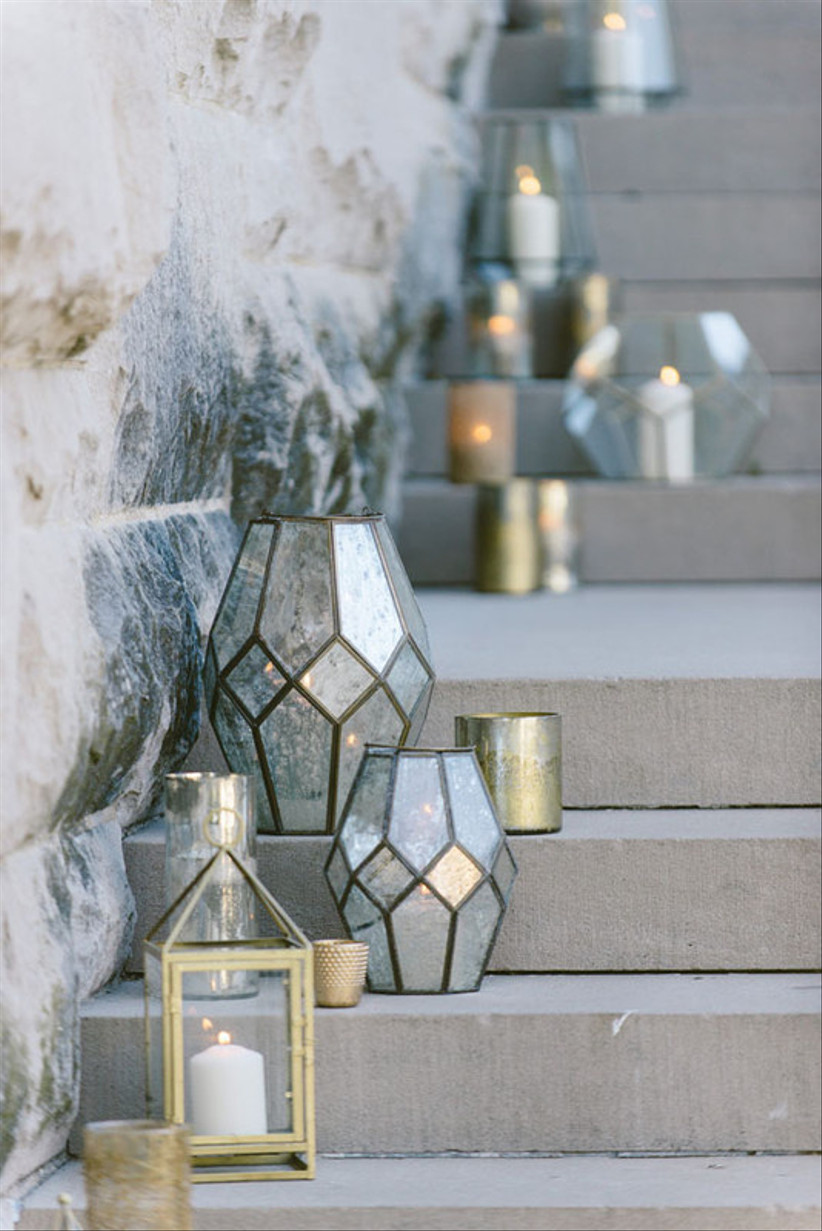 assorted silver and gold vases with candles decorate an outdoor staircase
