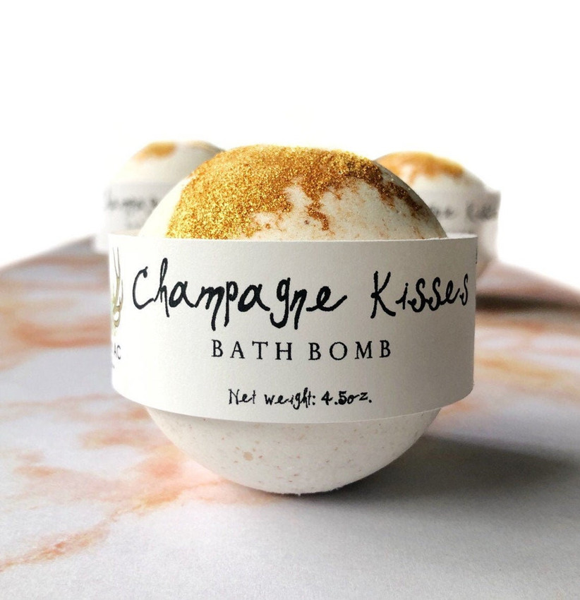Sparkly gold and white bath bomb with label reading Champagne Kisses