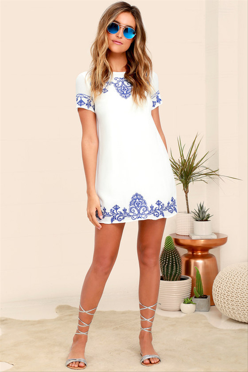 short white engagement party dress with blue embroidery on sleeves and hemline