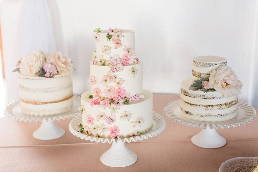 a trio of wedding cakes set on a table