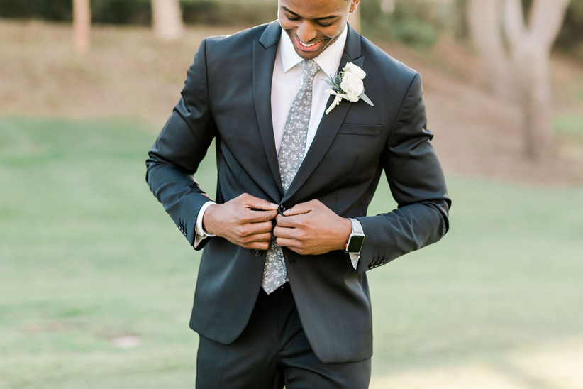 white rose wedding boutonniere with dark gray suit