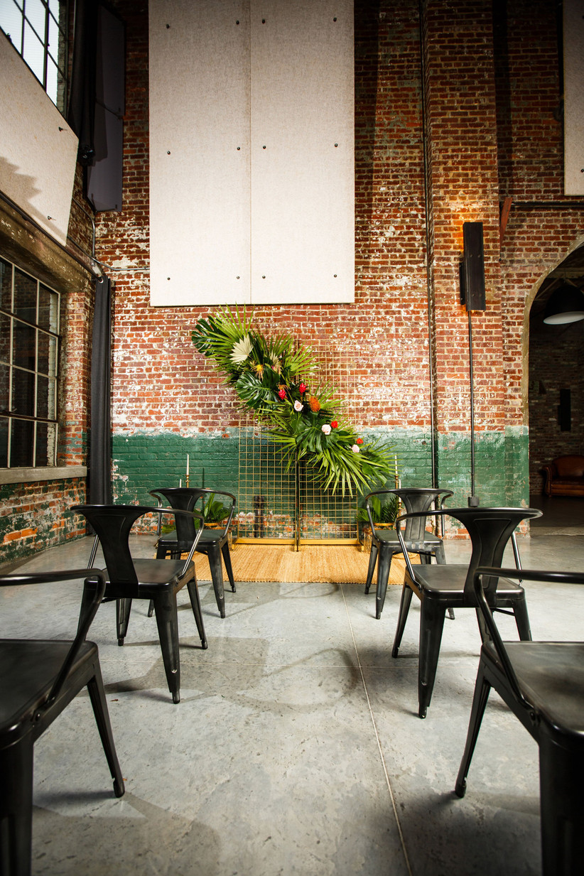 trending wedding ceremony backdrop with tropical flowers and greenery at industrial wedding venue