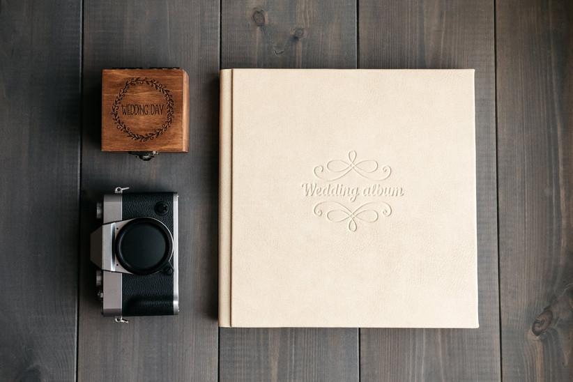 Off-white wedding photo album next to retro black camera and small wooden wedding keepsake box
