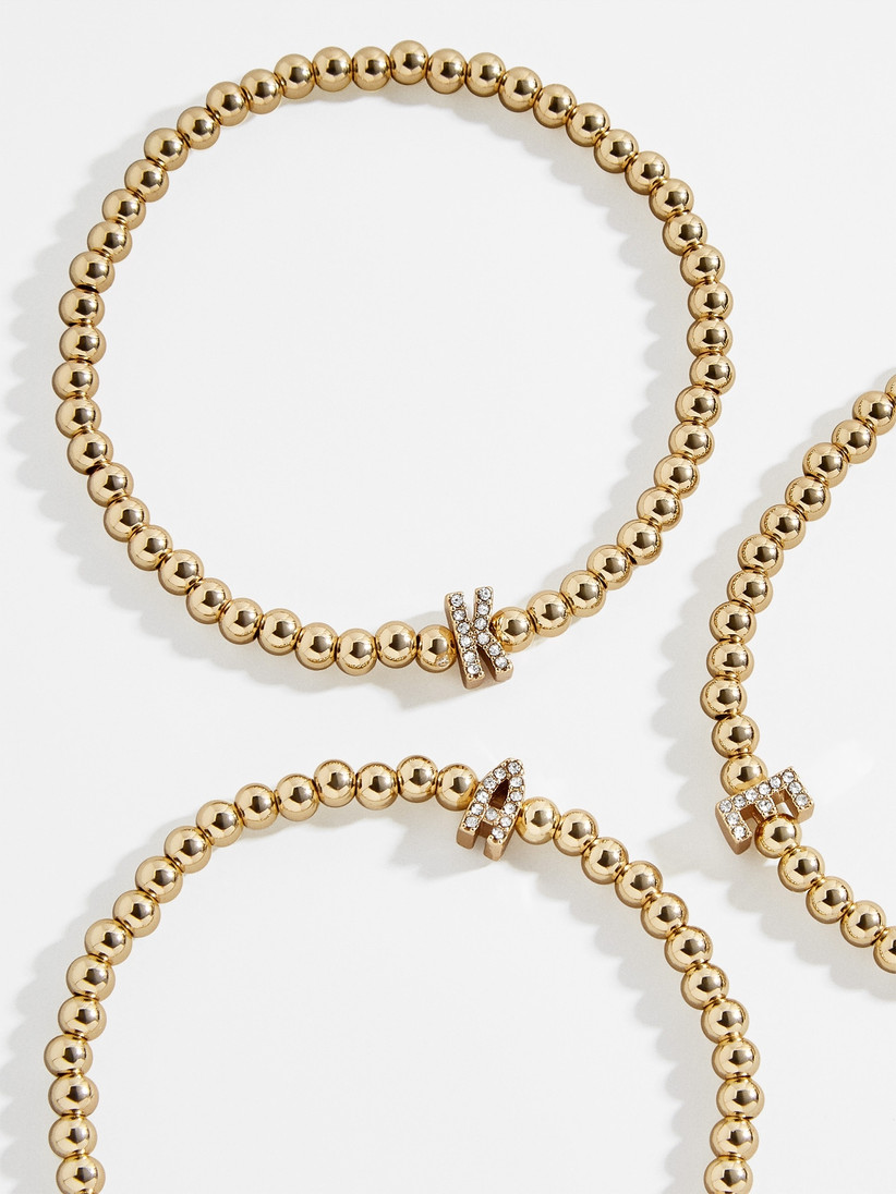 Three gold-beaded bracelets with different pavé initials