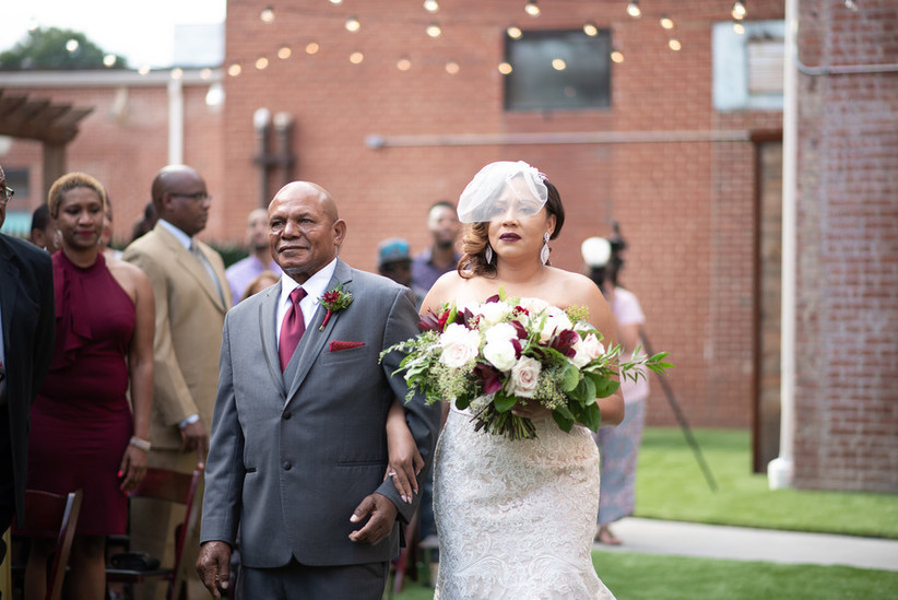 Bride and father walking down the aisle with guests watching wearing fall colors