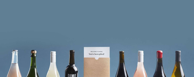 Bottles of wine in a row either side of Winc delivery box