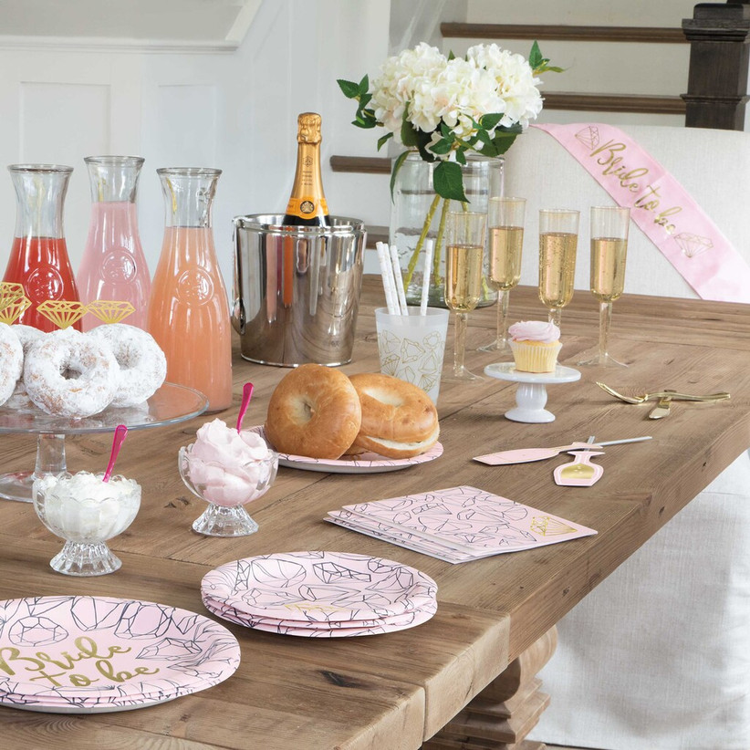 Celebratory bachelorette party table spread with drinks, champagne, donuts, and diamond-patterned paper plates and napkins
