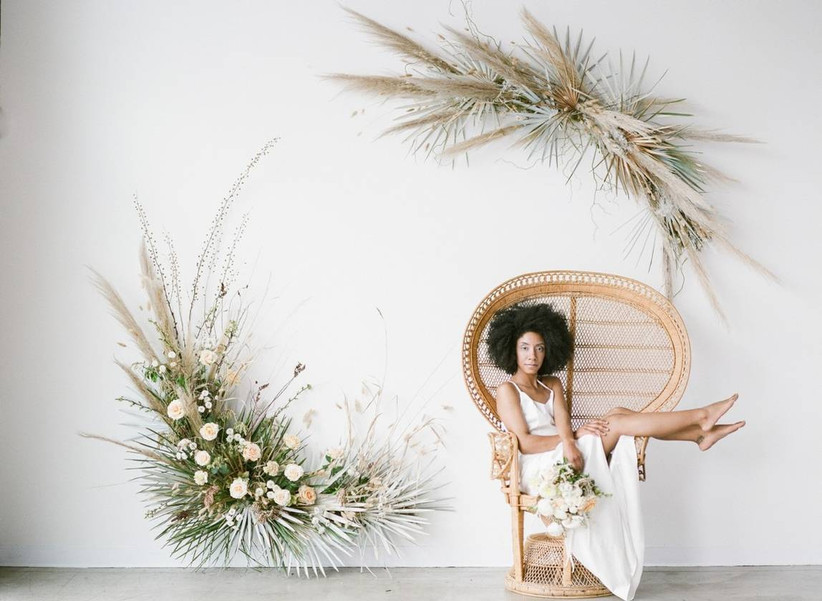 Black bride sitting in rattan peacock chair with trendy dried wedding flowers decorating the wall next to her
