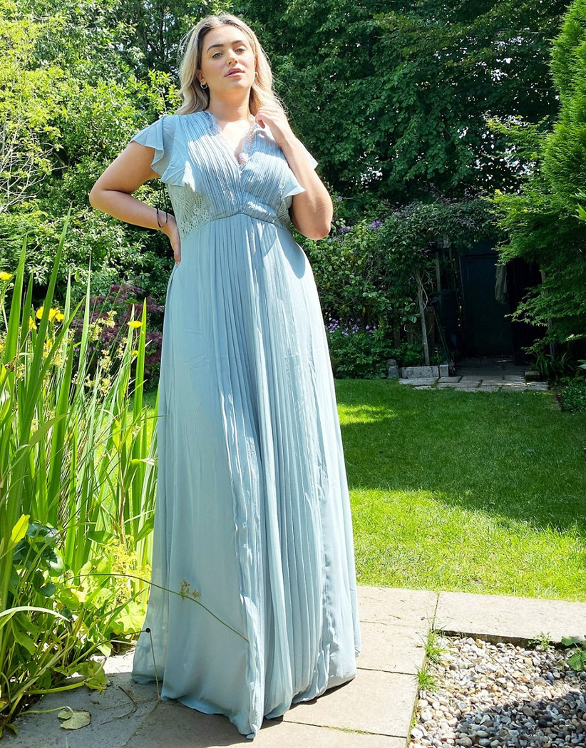 Model in garden wearing pastel blue bridesmaid dress with pleats and ruffled short sleeves
