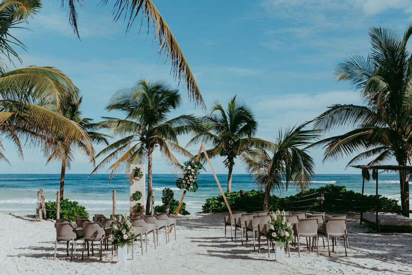 mexico beach wedding ceremony with triangle ceremony arch palm trees