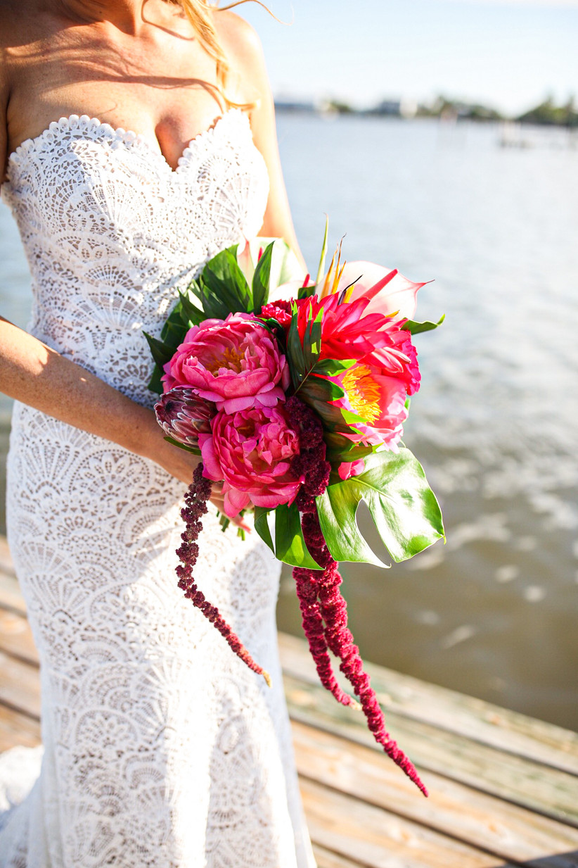bright pink and green beach wedding bouquet with peonies and monstera leaves
