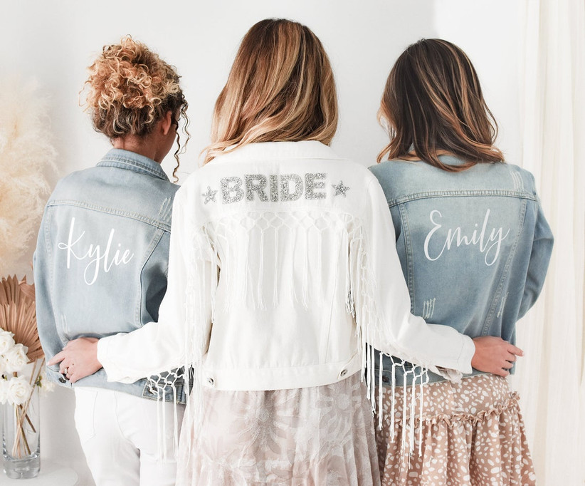 Bride wearing white denim Bride jacket turned away from the camera with her arms around bridesmaids wearing matching blue denim jackets personalized with their names