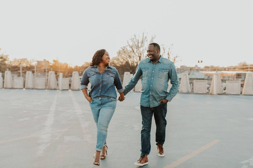 Black couple hold hands as they walk and smile at each other. They are wearing matching denim button-down shirts